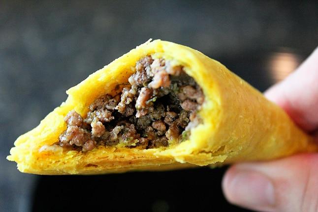 a half eaten jamaican beef pattie