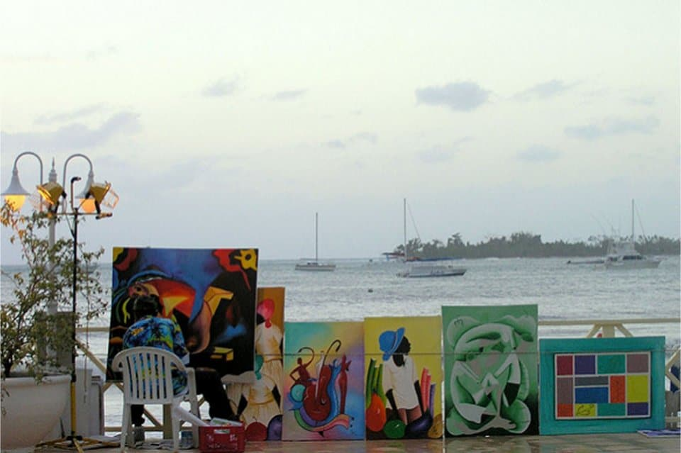Jamaican Artist painting on a bautiful bay, portraits of bright colors