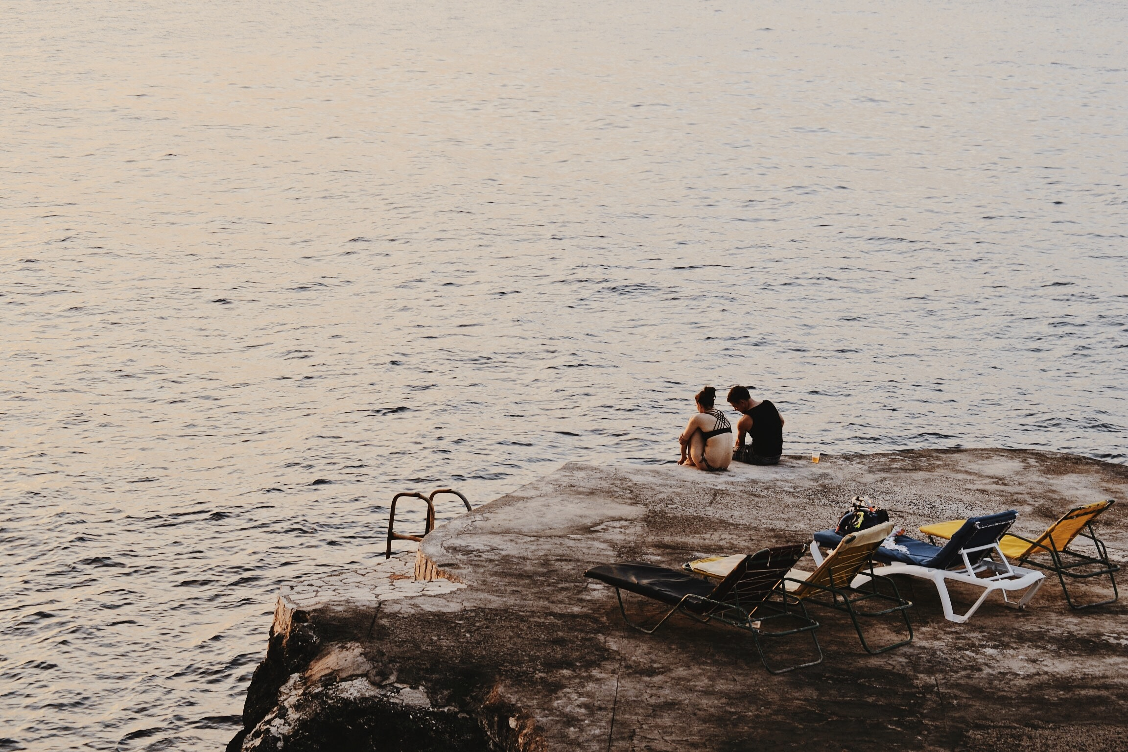 a couple sitting on the cliff located in Negril, Jamaica